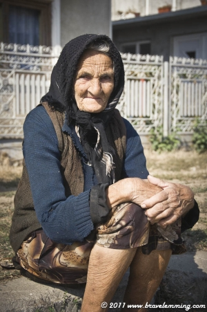 Old woman sitting on the pavement