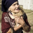 Old Romanian women holding her puppy