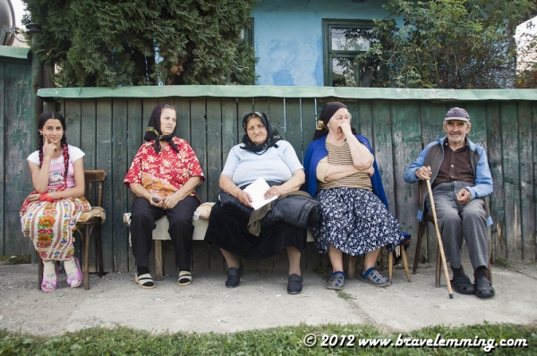 Locals sitting by the road in a village