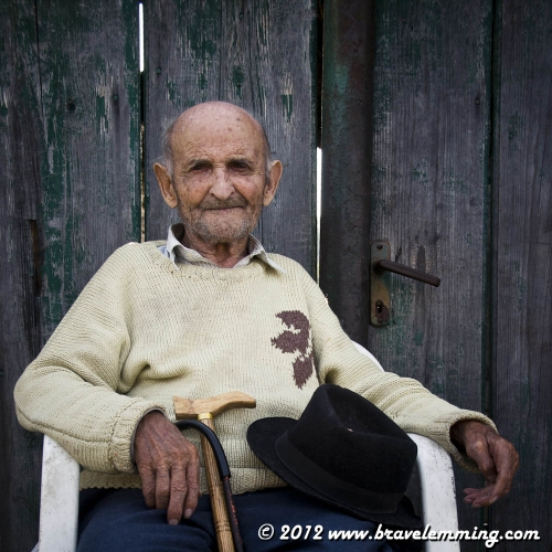 Portrait of an old man in front of his house