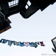 Above us, clothes are flying